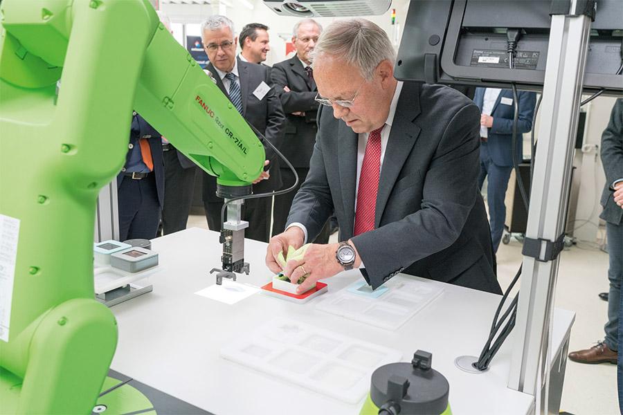 Bundesrat Schneider Ammen setzt an der Cobotic station Elekrtonische Produkte zusammen